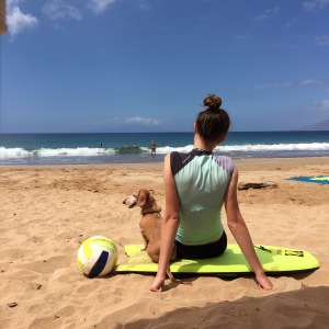 Girl sitting on boogie board on the beach